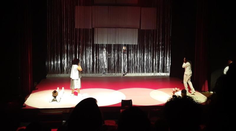 Em um palco de teatro, um homem vestido de branco está deitado, com as mãos no rosto. Uma mulher, de costas para ele, também com as mãos no rosto olha para outro homem, também vestido de branco.