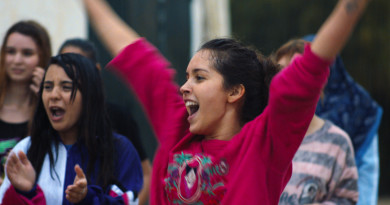 Na foto de fundo algumas mulheres desfocadas. A esquerda uma moça de cabelos longos lisos, boca aberta, vestindo um casaco vermelho, branco e azul, faz um gesto de aplauso. A frente a protagonista do filme, branca, de cabelos pretos presos em coque, de braços erguidos. Ela veste blusa de manga longa vermelha, e sorri.