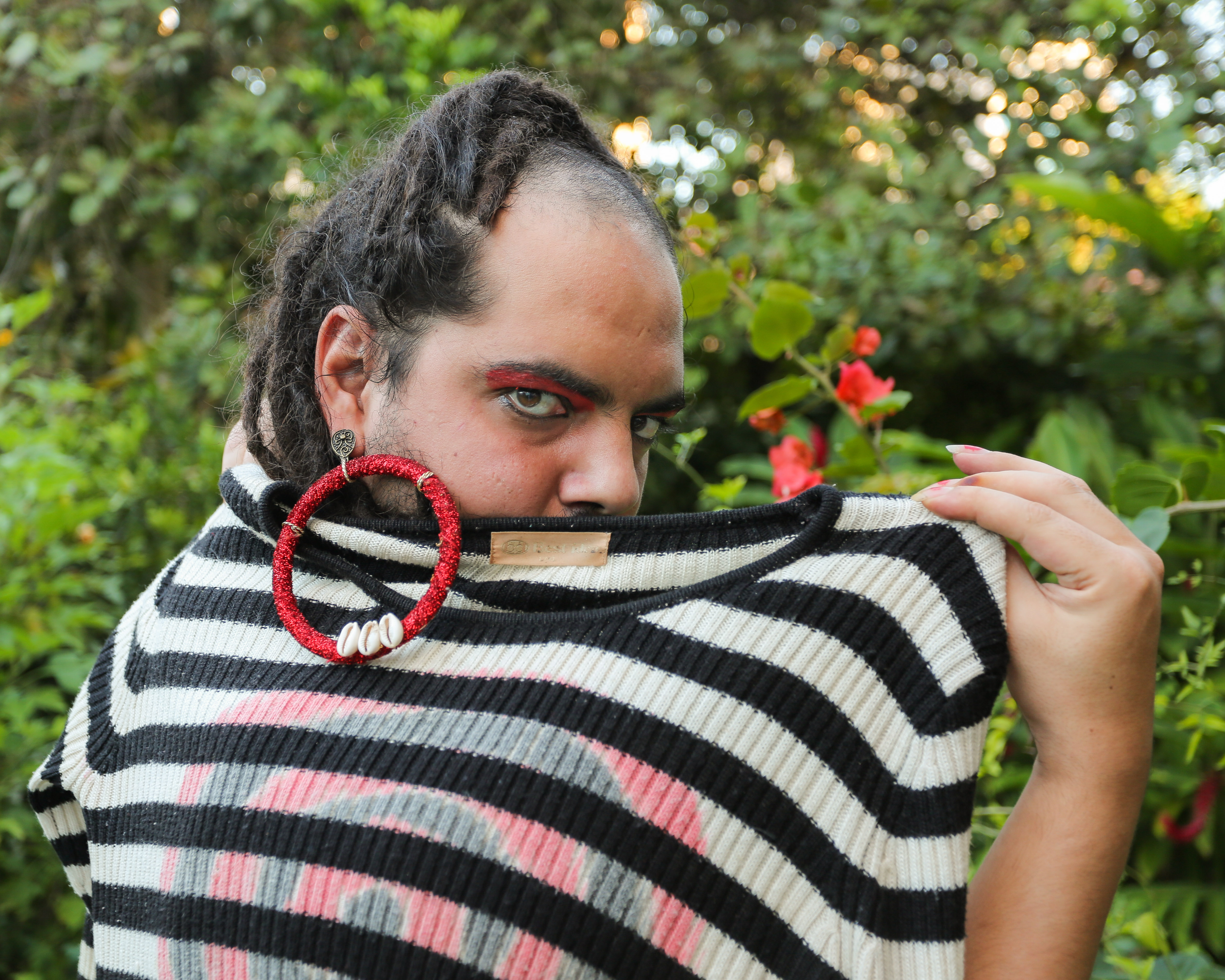 #PraCegoVer: Yuri Tripodi, mulher branca e de barba, olha de lado para a câmera. Ela usa brincos vermelhos e segura uma blusa listrada em preto e branco