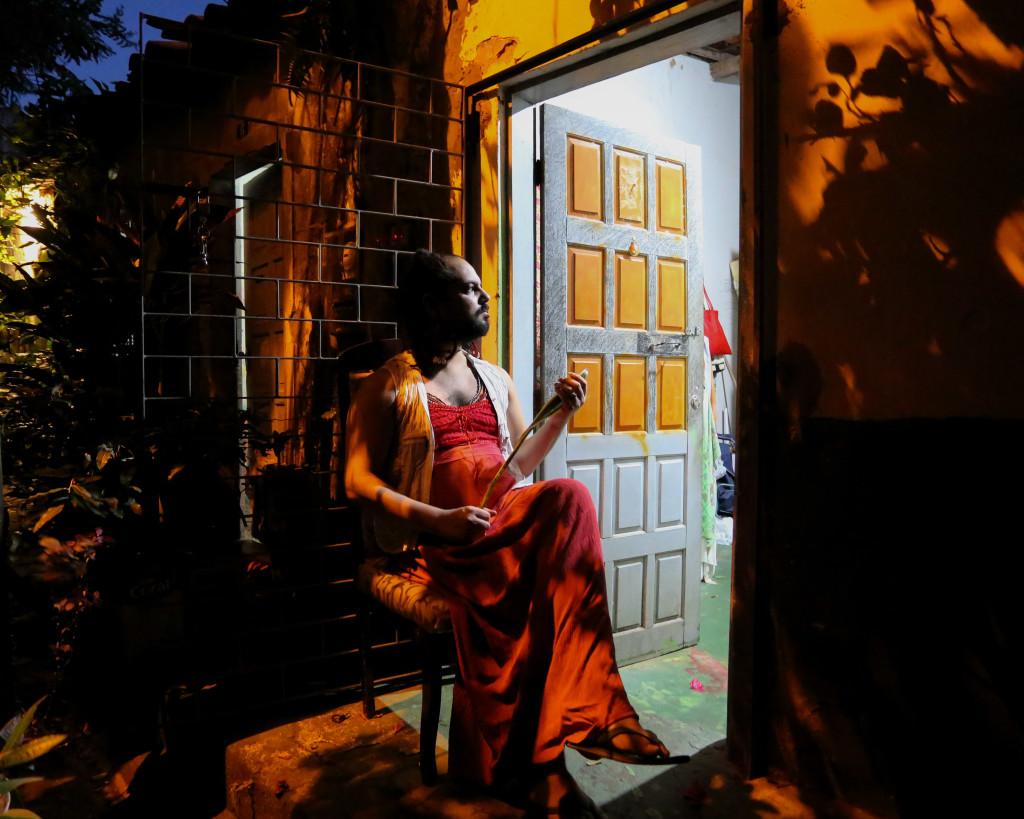 #pracegover: Foto noturna, sombras de plantas e casas ao fundo. No centro da imagem sentada de perfil, Yuri Tripodi, mulher branca de barba e cabelos castanhos está encostada na grade da porta de sua casa, ela veste vestido vermelho e colete branco. Segura uma planta, espada de Oxossi, nas mãos e está de pernas cruzadas e sandália. Seu rosto é iluminado pela luz que vem de dentro da casa, que está de porta aberta. A porta é azul clara, com nove quadrados amarelos pintados. A casa por dentro tem a parede azul e o chão verde.